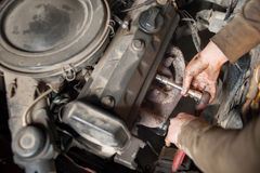 Hands of repairman mechanic working on engine using tool Royalty Free Stock Photos
