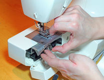 Hands replacing a bobbin in a sewing machine. Royalty Free Stock Photo