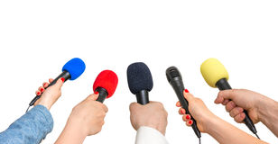 Hands of reporters with many microphones. Journalism and broadcasting concept - isolated on white Royalty Free Stock Photography