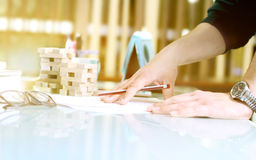 Hands rested on the table . Pencil held in one hand. Wooden blocks arranged in two piles in the background. Hands rested on the table . Pencil held in one hand Stock Image