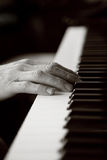 Hands resting on a piano keyboard Stock Photo