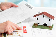 Hands reviewing real estate property documents. Close up of female hands reviewing real estate property documents Royalty Free Stock Photo