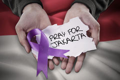 Hands with ribbon and text of Pray For Jakarta Stock Photo