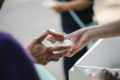 The hands of the rich are giving food to the poor and hungry stock photography