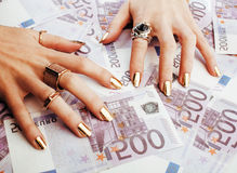 Hands of rich woman with golden manicure and many jewelry rings Royalty Free Stock Photos
