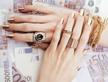 Hands of rich woman with golden manicure and many Royalty Free Stock Images