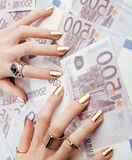 Hands of rich woman with golden manicure and many Stock Photo