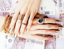 Hands of rich woman with golden manicure and many jewelry rings on cash euros Stock Images
