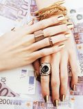 Hands of rich woman with golden manicure and many jewelry rings Stock Photos