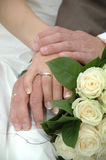 Hands, rings and bouquet. Wedding couple holding hands and a bouquet Stock Photography