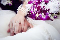 Hands and rings on bouquet Stock Photos