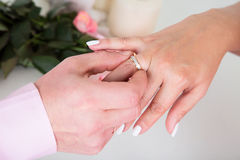 Hands with rings Groom putting golden ring on bride's finger dur Stock Photography