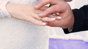 Hands with rings Groom putting golden ring on bride`s finger during wedding ceremony. Loving couple closeup stock footage