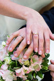 Hands and rings of just married on wedding bouquet Royalty Free Stock Images