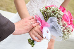Hands and rings with wedding bouquet Stock Photo