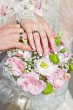 Hands and rings on wedding bouquet Stock Image