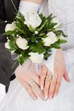 Hands with rings and wedding bouquet Stock Images
