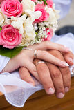 Hands and rings with wedding bouquet Stock Image