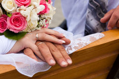 Hands and rings with wedding bouquet Stock Images