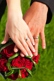 Hands with rings on wedding bouquet Royalty Free Stock Photo