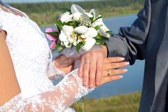 Hands and rings with wedding bouquet Royalty Free Stock Photo