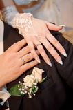 Hands with rings on wedding bouquet Royalty Free Stock Photography