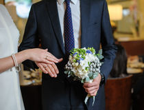Hands and rings on wedding bouquet Royalty Free Stock Images