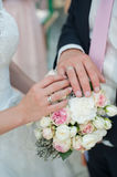 Hands with rings on a wedding bouquet background Stock Image