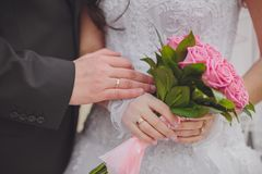 Hands and rings on the wedding bouquet Royalty Free Stock Image
