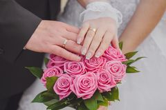 Hands and rings on the wedding bouquet Royalty Free Stock Photos
