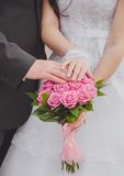 Hands and rings on the wedding bouquet Stock Photos