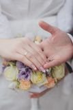 Hands and rings on the wedding bouquet Stock Photo