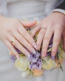 Hands and rings on the wedding bouquet Royalty Free Stock Photo