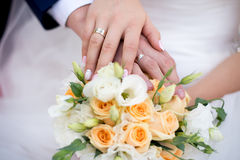 Hands and rings on wedding bouquet. Hands and rings of the bride and groom on wedding bouquet Stock Images