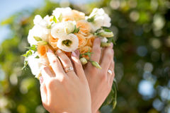 Hands and rings on wedding bouquet. Hands and rings of the bride and groom on wedding bouquet Stock Photos