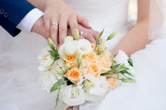 Hands and rings on wedding bouquet. Hands and rings of the bride and groom on wedding bouquet Royalty Free Stock Photography