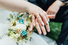 Hands and rings on wedding bouquet close up Royalty Free Stock Photos
