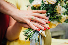 Hands and rings on wedding bouquet close up Royalty Free Stock Photography