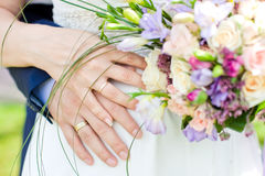 Hands and rings on wedding bouquet Stock Photos