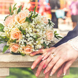Hands and rings on wedding bouquet Royalty Free Stock Image