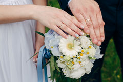 Hands and rings on wedding bouquet Stock Photography