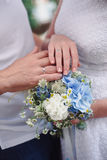 Hands and rings on wedding bouquet Royalty Free Stock Photography