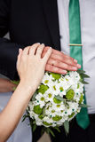 Hands and rings on wedding bouquet Stock Images