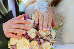 Hands and rings on wedding bouquet Stock Photo