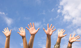 Hands rised up in air across  sky Stock Photos