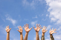 Hands rised up in air across  sky Royalty Free Stock Photography