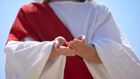 Hands in robe showing heart with cross, church praying for cardiac patients