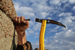 Hands rock-climber hammering in hook in rock Stock Photos