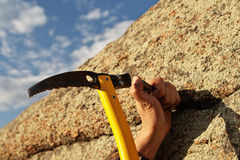 Hands rock-climber hammering in hook in rock. Blow by an ice axe on hand finger Royalty Free Stock Photography