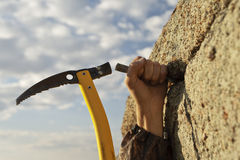 Hands rock-climber hammering in hook in rock. Work of the rock-climber against the sky and mountains Stock Image